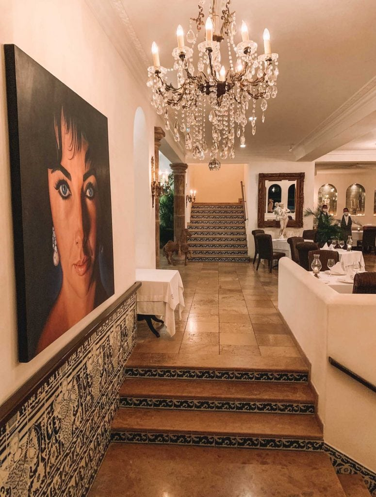 dining room with crystal chandelier and elizabeth taylor painting at the iguana restaurant in puerto vallarta