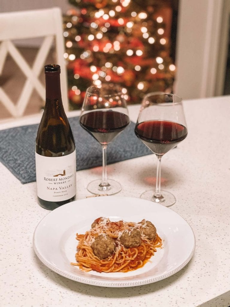 wine bottle and wine glasses with turkey meatballs and pasta from Pinch of Yum