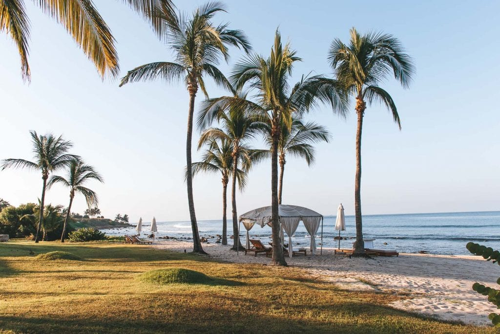 cabana with two chairs and palm trees on st regis punta mita beach
