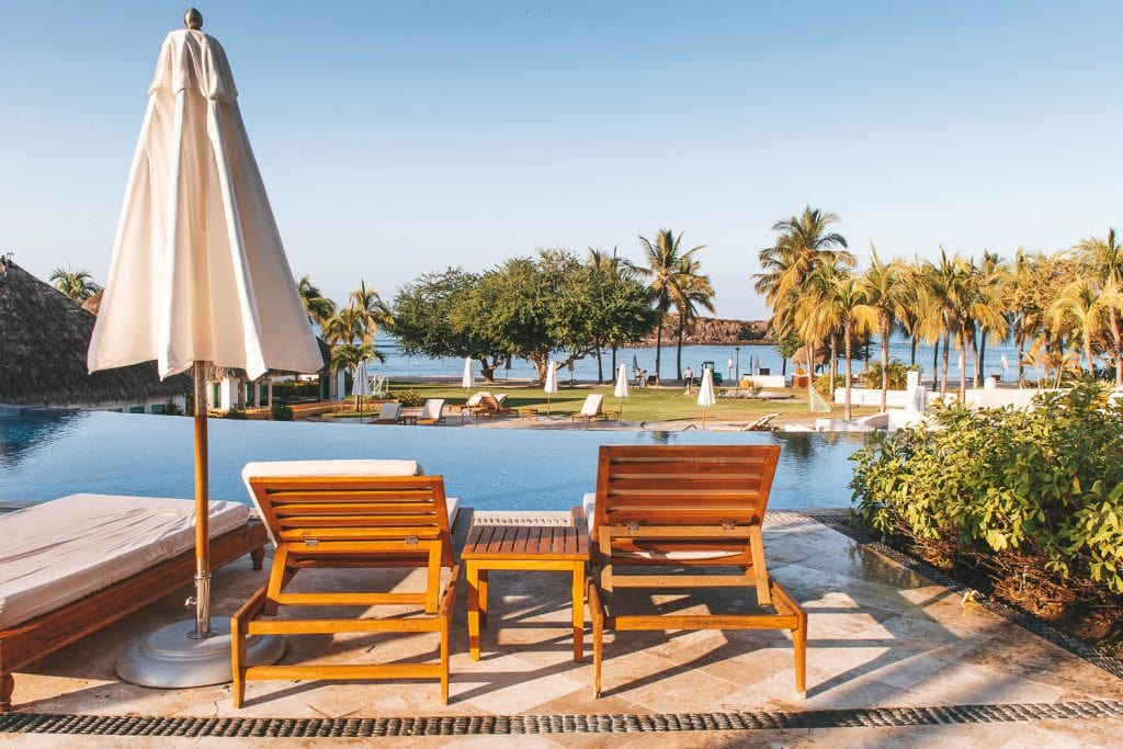 two lounge chairs with infinity pool and beach at the st regis punta mita resort
