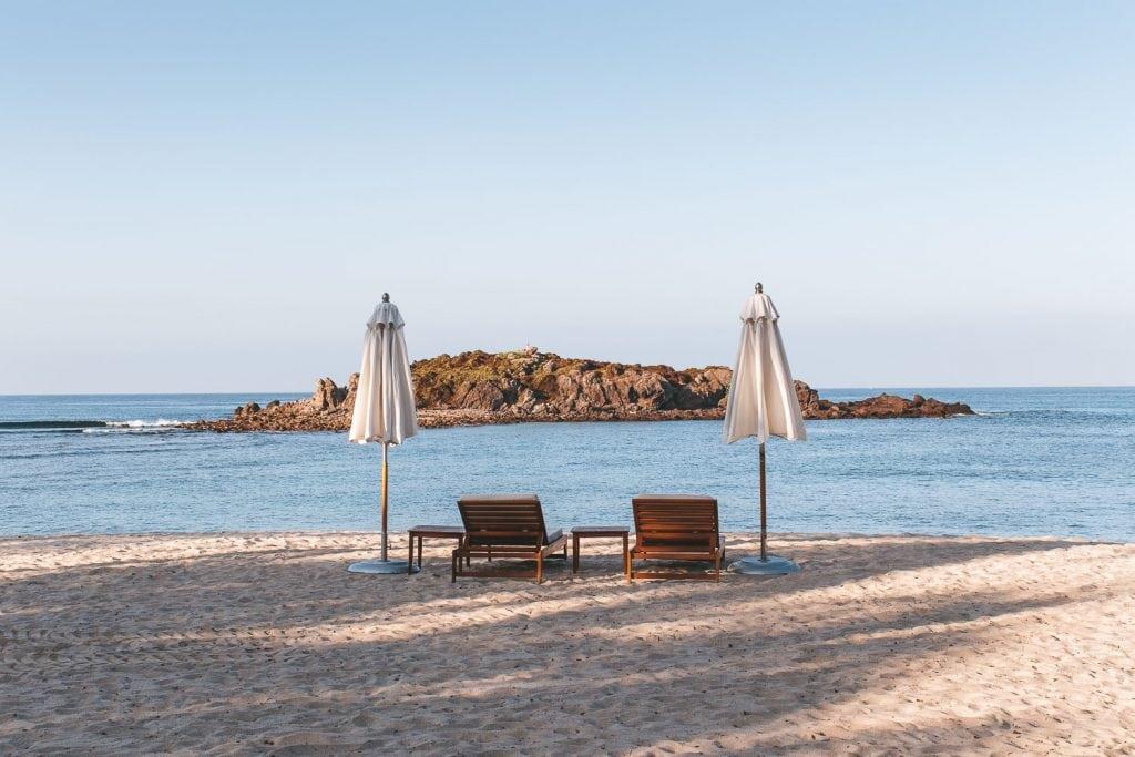 two beach chairs on beach looking into the ocean at st regis punta mita resort